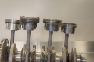 Krukas met vier verschillende TFSI-zuigers. Rechts de oorspronkelijke Audi-zuiger met de 1,5 mm lage olieschraapveer. Daarnaast de eerste Audi-modificatie met hogere olieschraapveer. Helemaal links de Hartog-zuiger met wafelstructuur olieschraapveer en daarnaast Audi's tweede modificatie met vergelijkbare structuur.